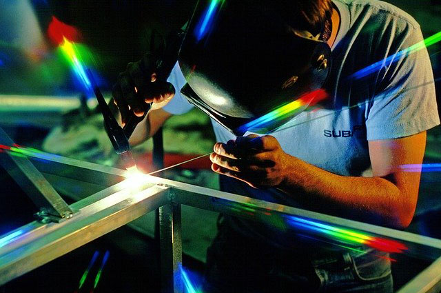 Guy welding in a workshop