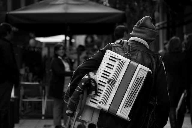 Musician with Accordion on his back walking on the street