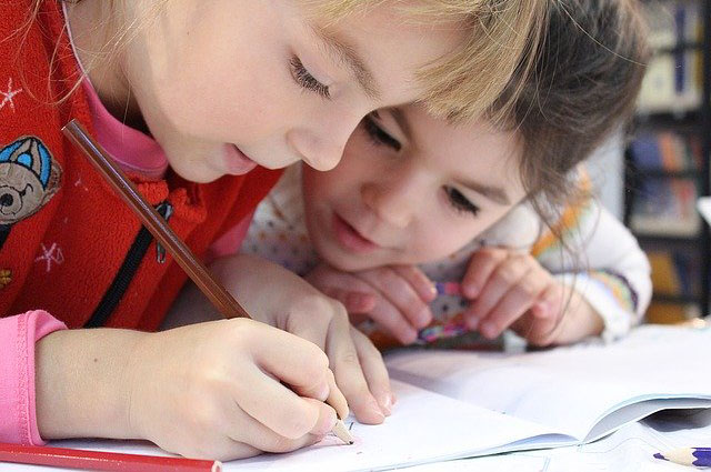 Two young students with pencil and book